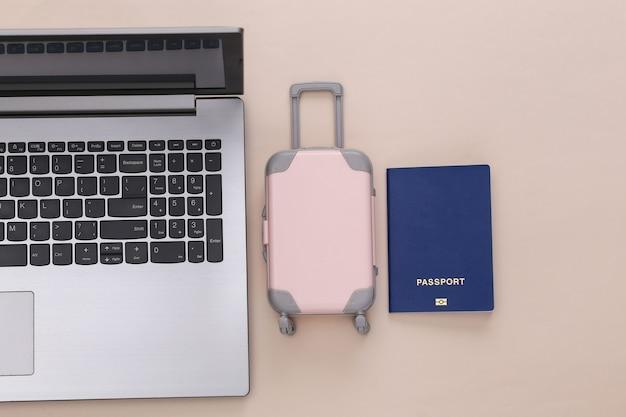 Plat lag vakantie vakantie en reizen schaven concept. laptop en mini plastic reiskoffer, paspoort op beige achtergrond. bovenaanzicht