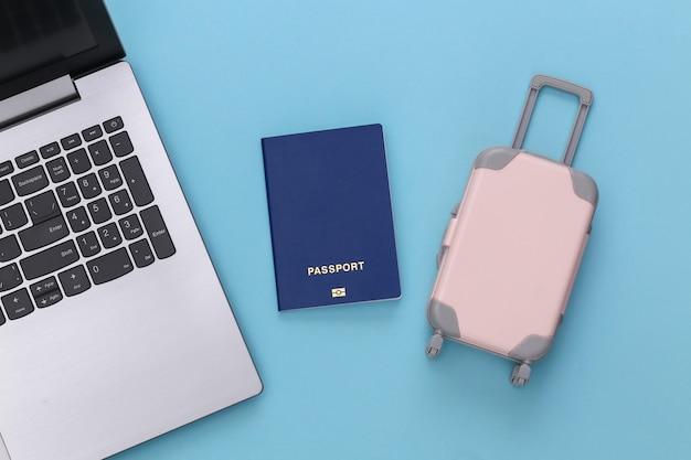 Plat lag vakantie vakantie en reizen schaven concept. laptop en mini plastic reiskoffer, paspoort op blauwe achtergrond. bovenaanzicht