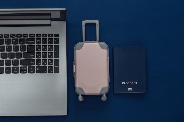 Plat lag vakantie vakantie en reizen schaven concept. laptop en mini plastic reiskoffer, paspoort op klassieke blauwe achtergrond. bovenaanzicht
