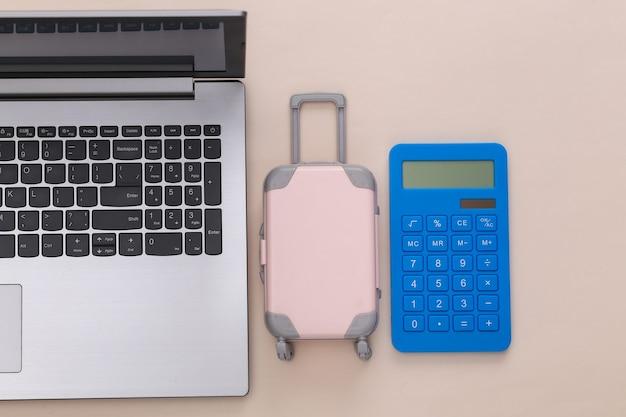 Plat lag vakantie vakantie en reizen schaven concept. laptop en mini plastic reiskoffer, paspoort, rekenmachine op beige achtergrond. bovenaanzicht