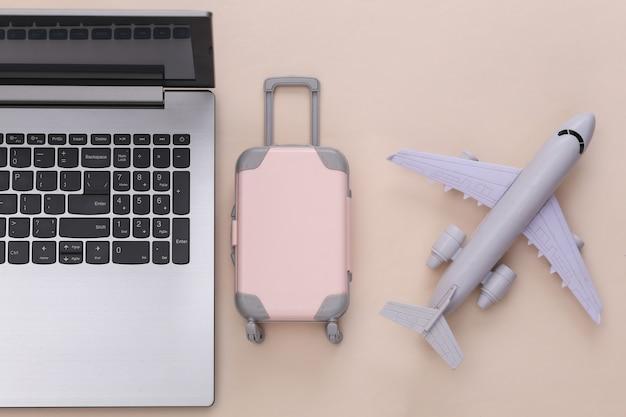 Plat lag vakantie vakantie en reizen schaven concept. laptop en mini plastic reiskoffer, paspoort, vliegtuig op beige achtergrond. bovenaanzicht