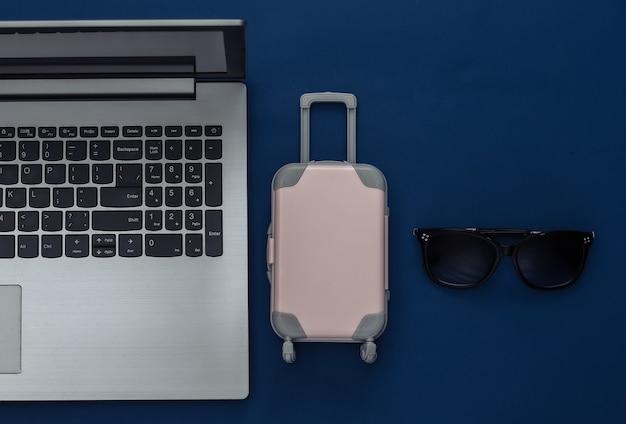 Plat lag vakantie vakantie en reizen schaven concept. laptop en mini plastic reiskoffer, paspoort, zonnebril op klassieke blauwe achtergrond. bovenaanzicht