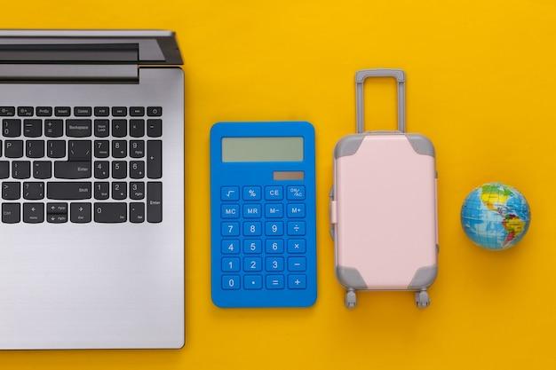 Plat lag vakantie vakantie en reizen schaven concept. laptop en mini plastic reiskoffer, rekenmachine, globe op gele achtergrond. bovenaanzicht