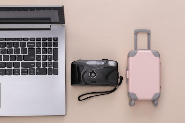 Plat lag vakantie vakantie en reizen schaven concept. laptop en mini plastic reiskoffer, rekenmachine op beige achtergrond. bovenaanzicht