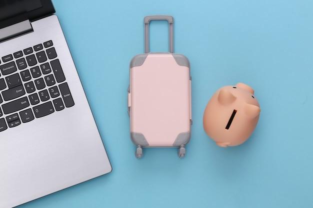 Plat lag vakantie vakantie en reizen schaven concept. laptop en mini plastic reiskoffer, spaarvarken op blauwe achtergrond. bovenaanzicht