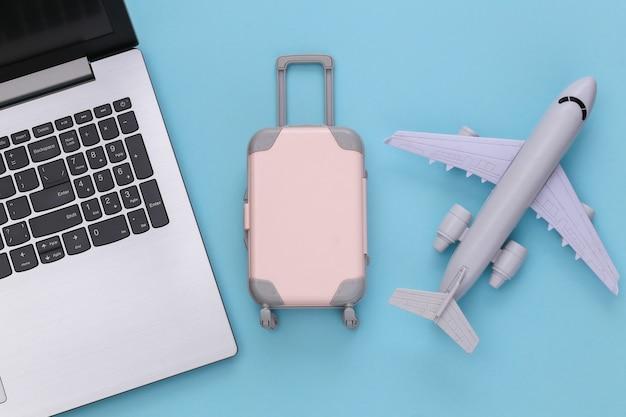 Plat lag vakantie vakantie en reizen schaven concept. laptop en mini plastic reiskoffer, vliegtuig op blauwe achtergrond. bovenaanzicht