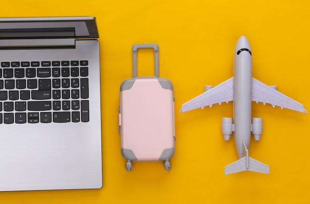 Plat lag vakantie vakantie en reizen schaven concept. laptop en mini plastic reiskoffer, vliegtuig op gele achtergrond. bovenaanzicht
