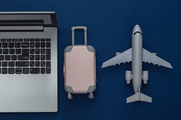 Plat lag vakantie vakantie en reizen schaven concept. laptop en mini plastic reiskoffer, vliegtuig op klassieke blauwe achtergrond. bovenaanzicht