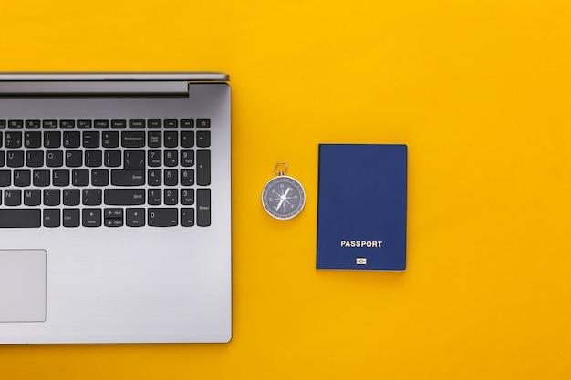 Plat lag vakantie vakantie en reizen schaven concept. laptop en paspoort, kompas op gele achtergrond. bovenaanzicht
