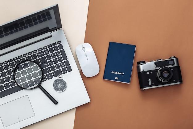 Plat lag vakantie vakantie en reizen schaven concept. laptop en reisaccessoires op beige bruine achtergrond. bovenaanzicht
