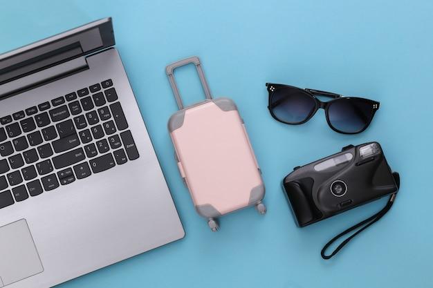 Plat lag vakantie vakantie en reizen schaven concept. laptop en reisaccessoires op blauwe achtergrond. bovenaanzicht