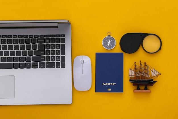 Plat lag vakantie vakantie en reizen schaven concept. laptop en reisaccessoires op gele achtergrond. bovenaanzicht