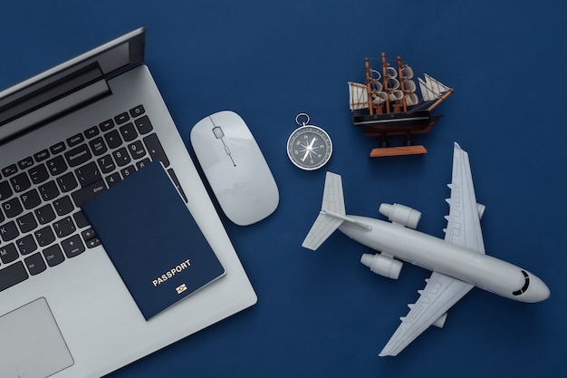 Plat lag vakantie vakantie en reizen schaven concept. laptop en reisaccessoires op klassieke blauwe achtergrond. bovenaanzicht