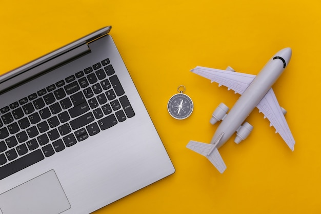 Plat lag vakantie vakantie en reizen schaven concept. laptop en vliegtuig, kompas op gele achtergrond. bovenaanzicht
