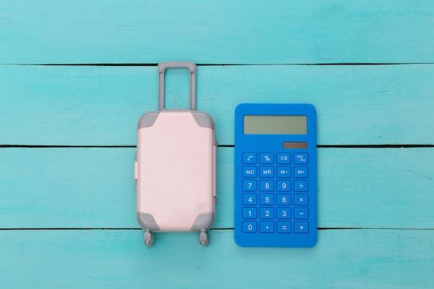 Plat lag vakantie vakantie en reizen schaven concept. mini plastic reiskoffer en rekenmachine op blauwe houten achtergrond. bovenaanzicht