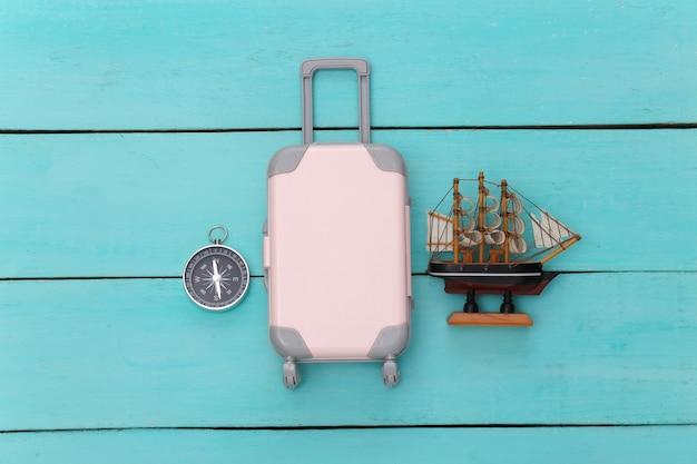 Plat lag vakantie vakantie en reizen schaven concept. mini plastic reiskoffer en schip, conmpass op blauwe houten achtergrond. bovenaanzicht