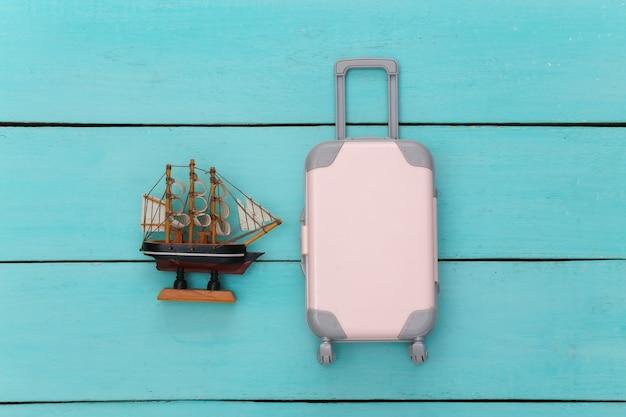 Plat lag vakantie vakantie en reizen schaven concept. mini plastic reiskoffer en schip op blauwe houten achtergrond. bovenaanzicht