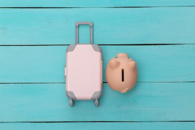 Plat lag vakantie vakantie en reizen schaven concept. mini plastic reiskoffer en spaarvarken op blauwe houten achtergrond. bovenaanzicht