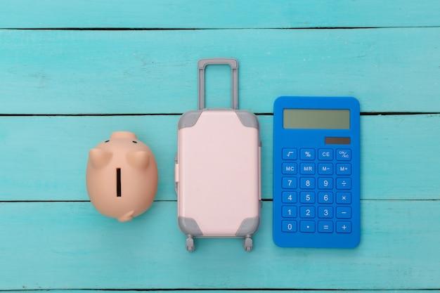 Plat lag vakantie vakantie en reizen schaven concept. mini plastic reiskoffer en spaarvarken, rekenmachine op blauwe houten achtergrond. bovenaanzicht