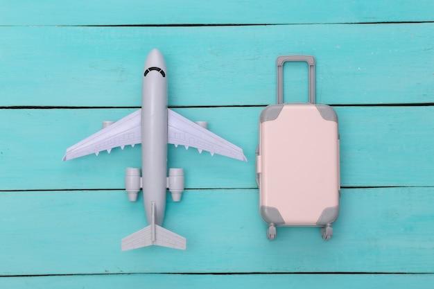 Plat lag vakantie vakantie en reizen schaven concept. mini plastic reiskoffer en vliegtuig op blauwe houten achtergrond. bovenaanzicht