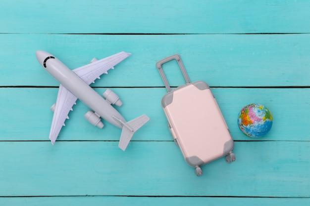 Plat lag vakantie vakantie en reizen schaven concept. mini plastic reiskoffer, globe en vliegtuig op blauwe houten achtergrond. bovenaanzicht