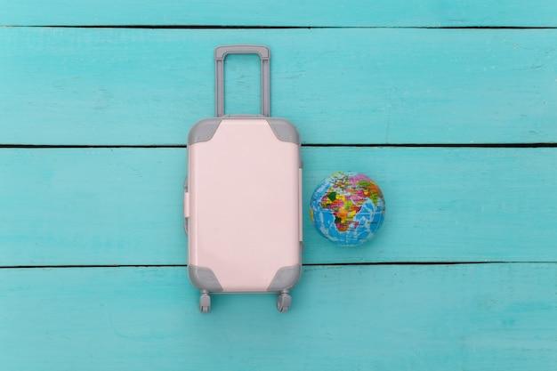 Plat lag vakantie vakantie en reizen schaven concept. mini plastic reiskoffer, globe op blauwe houten achtergrond. bovenaanzicht