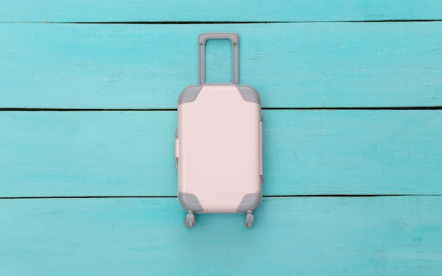 Plat lag vakantie vakantie en reizen schaven concept. mini plastic reiskoffer op blauwe houten achtergrond. bovenaanzicht