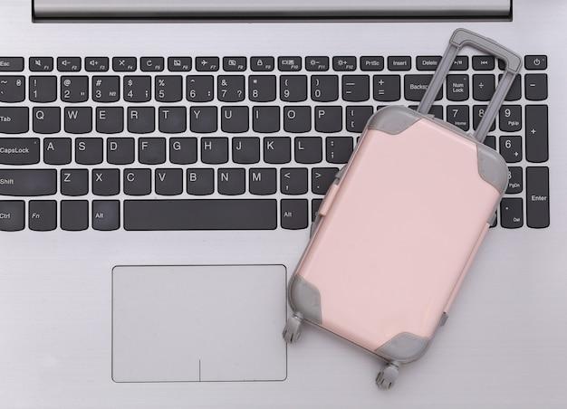 Plat lag vakantie vakantie en reizen schaven concept. mini plastic reiskoffer op laptop toetsenbord. bovenaanzicht
