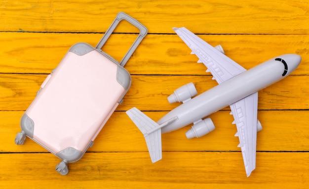 Plat lag vakantie vakantie en reizen schaven concept. mini plastic reiskoffer, vliegtuig op gele houten achtergrond. bovenaanzicht