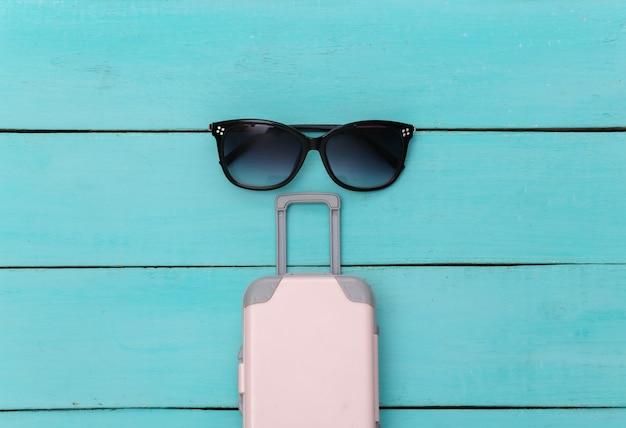 Plat lag vakantie vakantie en reizen schaven concept. mini plastic reiskoffer, zonnebril op blauwe houten achtergrond. bovenaanzicht
