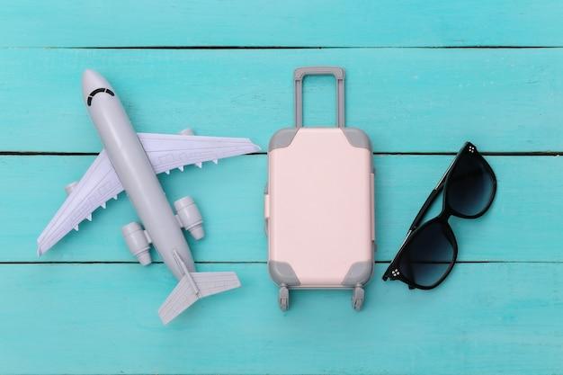 Plat lag vakantie vakantie en reizen schaven concept. mini plastic reiskoffer, zonnebril, vliegtuig op blauwe houten achtergrond. bovenaanzicht