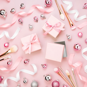 Plat lag vakantieachtergrond met kerstbal, cadeau, lint, make-upborstel en decoraties in pastelroze kleur. platliggend, bovenaanzicht