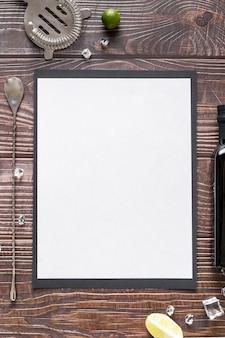 Plat lag van blanco menu papier op houten oppervlak met olijfolie