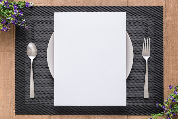 Plat lag van blanco menu papier op plaat met bloemen en bestek