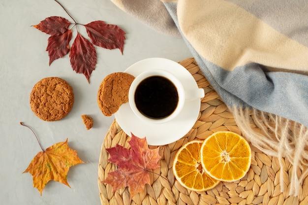 Plat lag van een kopje zwarte koffie op een grijs met herfstbladeren, een warme cape