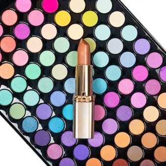 Plat lag van gouden lippenstift op kleurrijke oogschaduw palet