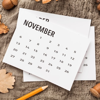 Plat lag van kalender met herfstbladeren en eikels