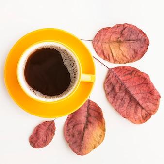 Plat lag van koffiekopje met herfstbladeren