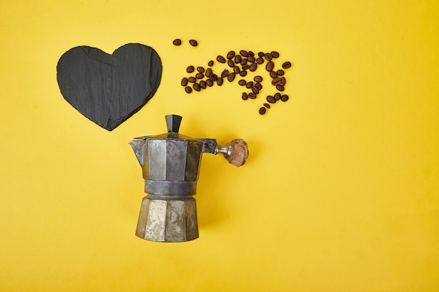 Plat lag van koffiezetapparaat en koffiebonen op gele achtergrond.