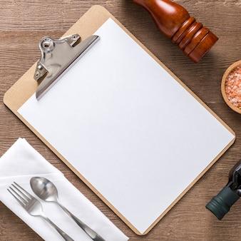Plat lag van leeg menu met olijfolie en bestek