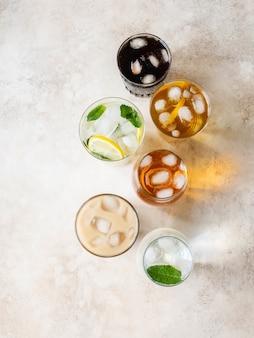 Plat lag van verschillende verfrissende drankjes in glazen met ijs