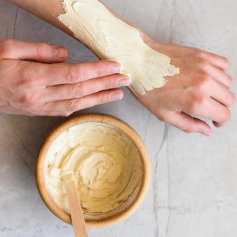 Plat lag van vrouw die lotion op haar handen toepast