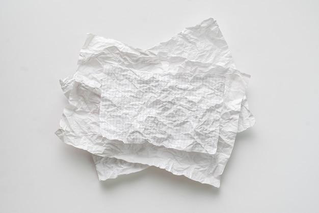 Plat lag verfrommeld wit vel papier geïsoleerd op de tafel, achtergrondstructuur