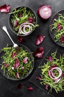 Plat lag verse salades op donkere borden