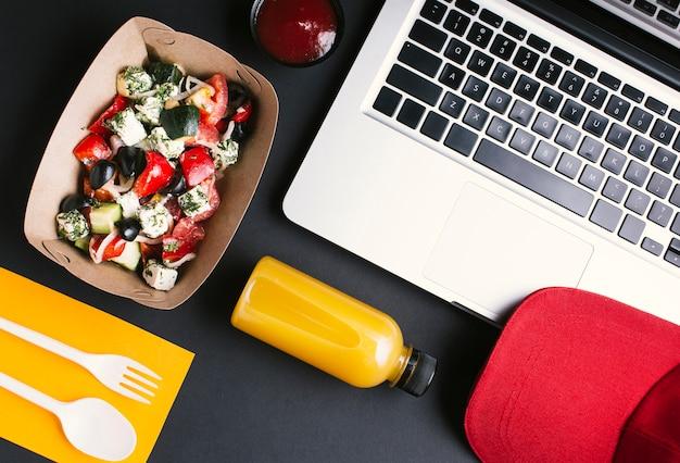 Plat lag voedsel en laptop op zwarte achtergrond
