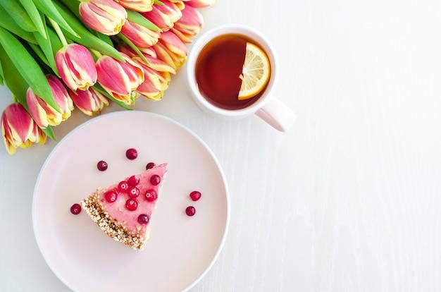Plat lag voor ontbijt, ochtend met bloemen tulpen, cake, thee in roze mok op witte achtergrond.