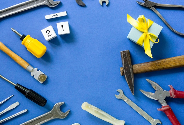Plat lag voor vaderdag met gereedschap en geschenkdoos op een blauwe achtergrond