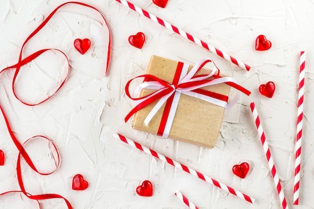 Plat lag voor valentijnsdag met rode harten, kaarsen, confetti op wit.