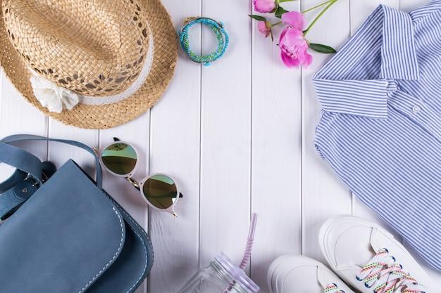 Plat lag vrouw zomerkleding en accessoires collage op wit met shirt, spijkerbroek, bril, schoenen, handtas, hoed, pot