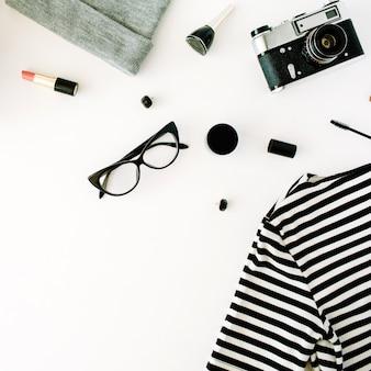 Plat lag vrouwelijke herfst en winterkleren collage met retro camera, accessoires en cosmetica op wit